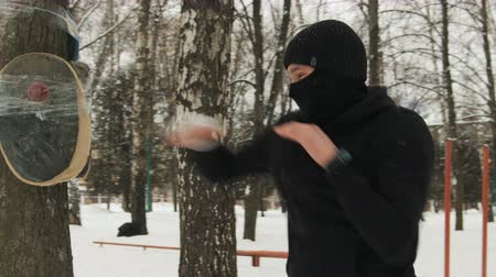 powerful : A young kickboxer guy with bandages on his hands, in a black suit trains in the fresh air in winter. He made a mannequin in a tree Stock Footage