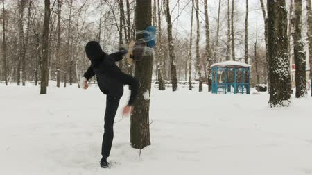 kickbox : A young kickboxer guy with bandages on his hands, in a black suit trains in the fresh air in winter. He made a mannequin in a tree Dostupné videozáznamy