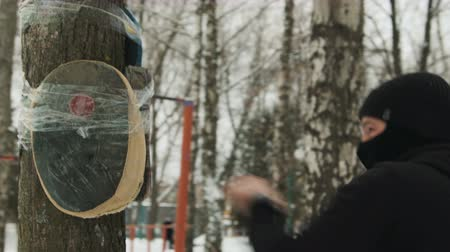 balaclava : A young kickboxer guy with bandages on his hands, in a black suit trains in the fresh air in winter. He made a mannequin in a tree Stock Footage