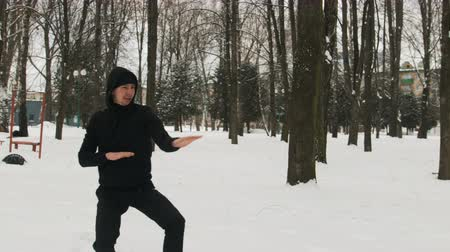 戦闘 : One young guy in a black suit during karate training, kata exercise in winter outdoors 動画素材