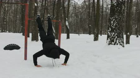 гимнаст : Street workout equipment in winter, outdoor sport fitness and bodybuilding. Boy in a sport playground doing workout exercises outdoor in winter.
