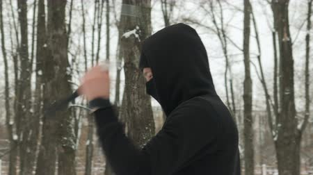 balaclava : A handsome young man in a black suit and balaclava demonstrates mastery with nunchucks in an outdoor winter park. Goes in for sports and has fun Stock Footage
