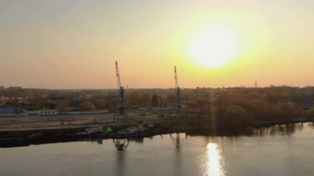pontile : Aerial view of the river port with two cranes and tugs ships in the setting sun. The concept of crisis, downtime, work interruption