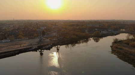 подъемник : Aerial view of the river port with two cranes and tugs ships in the setting sun. The concept of crisis, downtime, work interruption