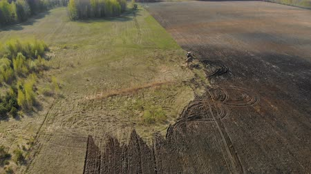 zatáčka : Aerial view of a powerful, energy-saturated tractor of red color with a large hook force pulling a multi-turn plow, cultivator with ploughshares on the background of picturesque nature. Tillage before sowing crops Dostupné videozáznamy