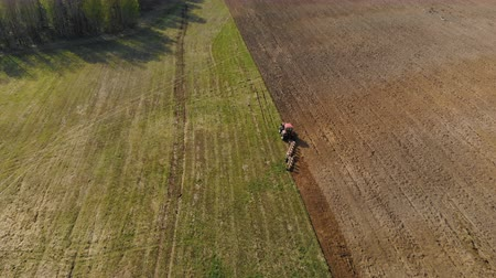 powerful : Aerial view of a powerful, energy-saturated tractor of red color with a large hook force pulling a multi-turn plow, cultivator with ploughshares on the background of picturesque nature. Tillage before sowing crops Stock Footage