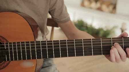 string instrument : Dolly shot close-up of the hands of a young man playing guitar. Camera movement along the instrument neck with working fingers and vibrating strings Stock Footage