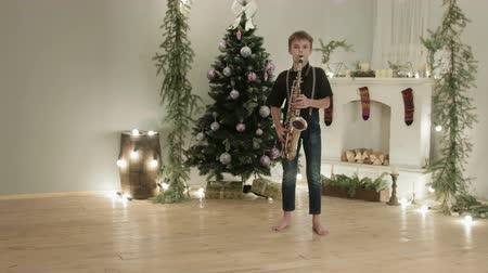 divino : Dolly shot a boy in dark jeans and shirt playing saxophone in a room with Christmas atmosphere, decoration. The concept of the celebration, the new year Stock Footage