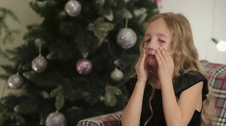 украшенный : A blond girl in a black dress cries and wipes her tears for the new year near the Christmas tree decorated with colorful balls, because she did not receive a gift