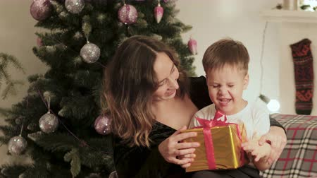 pudełko : Happy, smiling mother and child on Christmas tree background. mom gives her son a beautiful gift. Family holiday, new years concept Wideo