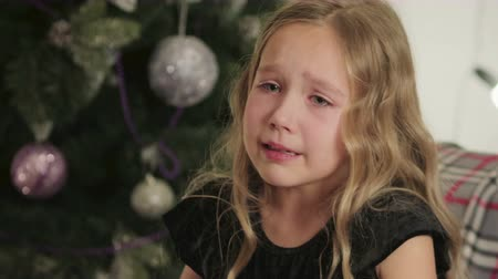níveis : A blond girl in a black dress cries and wipes her tears for the new year near the Christmas tree decorated with colorful balls, because she did not receive a gift
