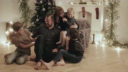 atmosféra : Dolly shot a large, friendly, loving family of five, father, mother, two sons and daughter, chatting in a room at home amid Christmas decorations and a fireplace. The concept of a fun holiday, new year