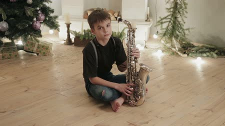 pudełko : Dolly shot a young boy musician, saxophonist sitting on the floor in the room of the house on the background of Christmas decorations, holiday tree with gift boxes and fireplace. The concept of a fun new year Wideo