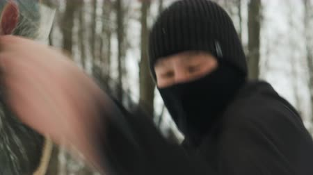 戦闘 : Steadicam shot closeup male fighter of martial arts, performing punches, protected with elastic bandages for soft items attached with tape to the tree. The concept of winter sports