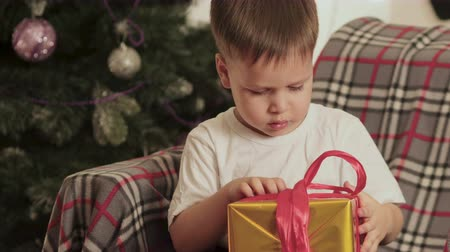 pudełko : Happy, little baby sitting under the Christmas tree on the chair at home and opens his gift. Christmas, winter miracles. The concept of new year