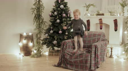 karácsonyi ajándék : Beautiful baby fun jumping and laughing in the chair for the new year. The room is decorated with lights and balls, there is a Christmas tree Stock mozgókép