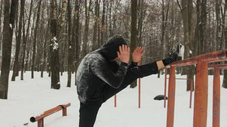 растягивание : Steadicam shot purposeful man in a black tracksuit with a hood, performing the stretching of the leg muscles on the old, vintage the bar. The concept of physical education in the open air in the winter, snow-covered Park Стоковые видеозаписи