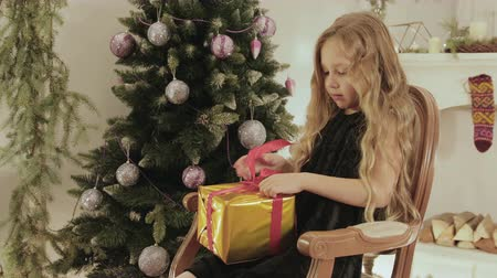 украшенный : Charming little girl unwraps a gift near the Christmas tree on Christmas eve at home. Interior decorated living room with a fireplace in the background