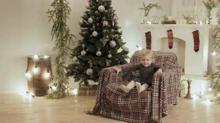 украшенный : Beautiful baby fun jumping and laughing in the chair for the new year. The room is decorated with lights and balls, there is a Christmas tree Стоковые видеозаписи