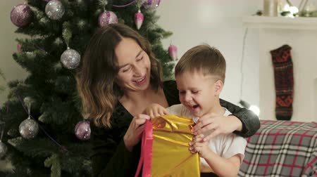 presentes : A young mother and her cute little son unwrap the gift in a bright, Golden package sitting on the couch near the Christmas tree. The boy is surprised and happy. The concept of new year Stock Footage