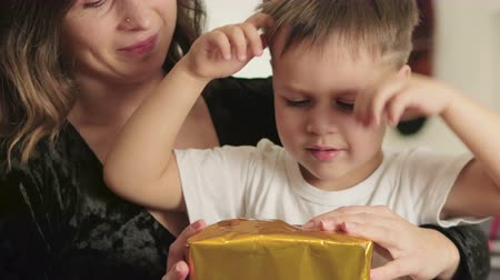 pudełko : A young mother and her cute little son unwrap a gift in a bright, gold package. The boy is surprised and happy. The concept of holiday and celebration