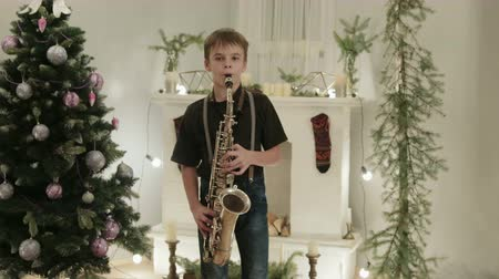instrumenty : Young saxophonist shows his Christmas performance on the instrument. It is in a beautiful, decorated room with a Christmas tree. The concept of new year