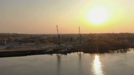 vessels : Industrial pier with floating docks on the river, moored river tugs, large cranes for unloading and loading barges. Aerial view at sunset