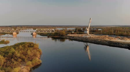 arame : Beautiful, panoramic view from above the bridge over the river and the crane in the city. In the winding river reflected crane. River construction
