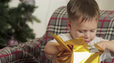 köknar ağacı : A cute happy boy unwraps a Christmas gift for a holiday in the morning in a beautiful room interior. The boy opens Christmas gifts near a large decorated Christmas tree. Winter holidays concept
