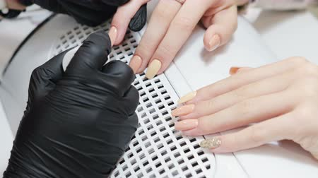 щеткой : Manicurist in black gloves wears nail Polish the client with beige nail Polish. The concept of a beautiful manicure