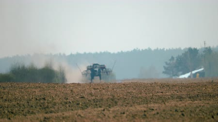 боке : Blurred image of the silhouette of an agricultural tractor with a seeder going to work on a dirty field with brown soil in hot, dry weather