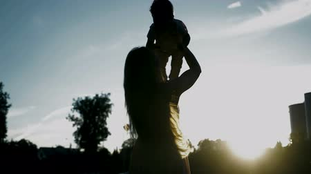 vychovávat : Silhouettes at sunset, a young mother and a young son. Mom lifts up and circles her baby. Happy family