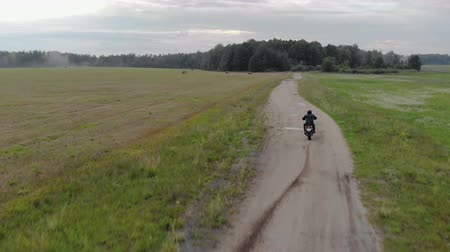védősisak : Aerial shot rear view of a young man, a biker in a black protective suit and helmet performing driving with the slip of the rear wheel on a rural dirt road