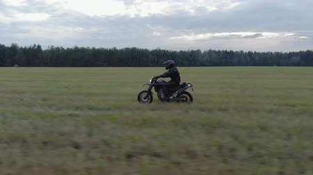 motor vehicle : Aerial shot extreme driving Enduro over rough terrain. A man in black protective gear controls a motorcycle riding at high speed on the field along the forest