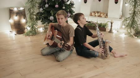 полоса : Dolly shot two kids, boys with musical instruments, guitar and saxophone playing music on fireplace background and Christmas decor. The concept of a new year