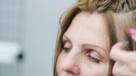 żelazko : Close-up of the head of an adult European woman with problem skin, dandruff in her hair. Client at the hairdressers reception Wideo
