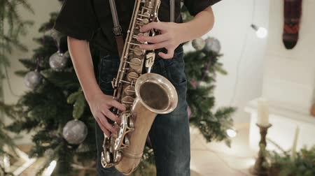 saxofone : Close-up of a child, a boy with a musical instrument, saxophone, playing music on the background of Christmas decor. New year song concept