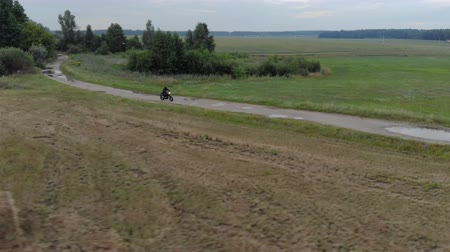 solo : Aerial shot of a side view of a young man, a motorcyclist in a black protective suit and helmet performing extreme driving with a rear wheel slip on a rural dirt road