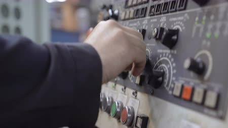 стабильность : Close-up of the hand of a man working pressing the buttons of the old control panel with the display. Equipment at the machine-building plant