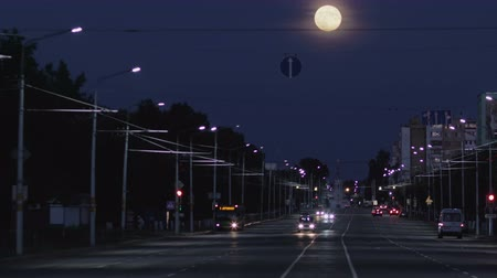Timelapse full moon rising above the highway with car traffic and the night city Стоковые видеозаписи