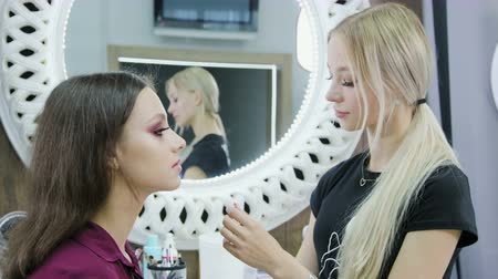 Makeup artist works with a brush on the models face. Portrait of a young brunette in a beauty salon interior. Applying a tone to the skin.