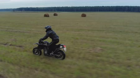 Aerial view extreme driving over rough terrain. Man in black protective gear standing controls motorcycle traveling at high speed on an agricultural field among bales of straw, along the misty forest Стоковые видеозаписи