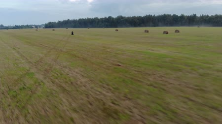 Aerial view extreme driving over rough terrain. Man in black protective gear standing controls motorcycle traveling at high speed on an agricultural field among bales of straw, along the misty forest Stock Footage
