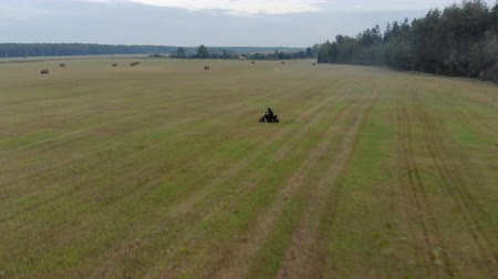 solo : Aerial view of the motorcyclist on a black motorcycle with the included headlight, extreme driving with a slip and skid on the agricultural field among the rolls of straw