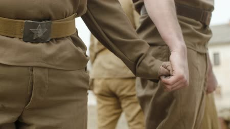 戦闘 : Steadicam shot close-up of soldiers in world war II uniform brown holding hands. The concept of brave warriors 動画素材