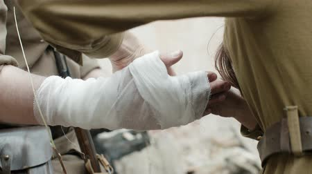 combate : Handheld shot dressing the wounded. Close-up of nurses and soldiers in the form of world war II, bandaging the hand of a soldier Smoking a cigarette