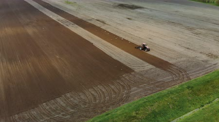 Aerial view of a farmer in a Tractor preparing the soil with a cultivator seedbed in picturesque farmland. The agricultural machine is followed by many white and black birds