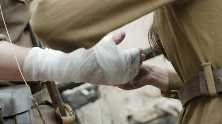 Handheld shot dressing the wounded. Close-up of nurses and soldiers in the form of world war II, bandaging the hand of a soldier Smoking a cigarette