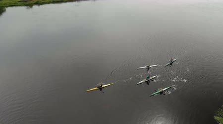 Aerial view of a group of five people traveling by kayak on a deep river in the spring against the backdrop of picturesque scenery