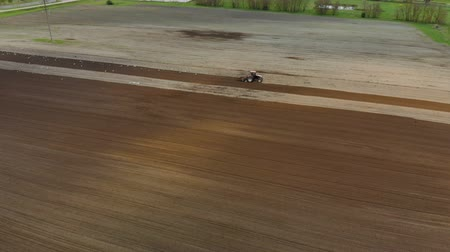 földműves : Aerial view of a farmer in a Tractor preparing the soil with a cultivator seedbed in picturesque farmland. The agricultural machine is followed by many white and black birds
